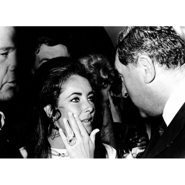 Elizabeth Taylor talking to a man Poster