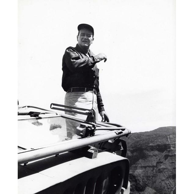 John Wayne standing behind a vehicle Poster