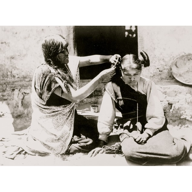 Kneeling Hopi woman combing and arranging hair of young girl. Poster